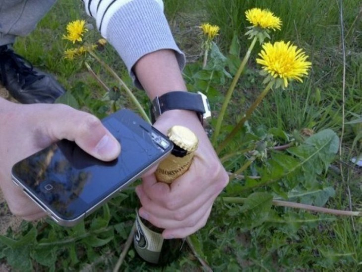 Persona abriendo una cerveza con un celular