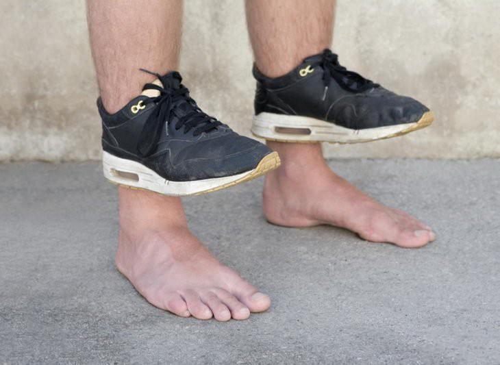 Pies de una persona con tenis hasta los tobillos